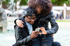 African couple in city looking up info an phone Stock Photos