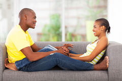 African couple couch. Cute young african couple sitting on the couch indoors Royalty Free Stock Images