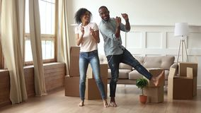 African couple first time home buyers dancing in living room