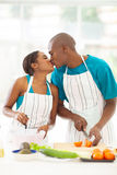 African couple kissing in kitchen stock photo