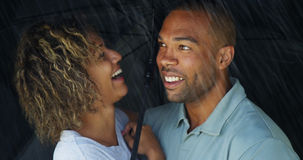 African couple laughing under umbrella together Royalty Free Stock Image