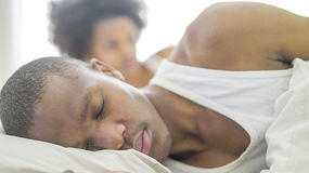 African couple lying in bed Stock Photo