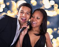 African Couple Singing With Microphone Stock Photo