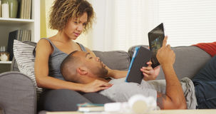 African couple using tablets on couch Royalty Free Stock Photo