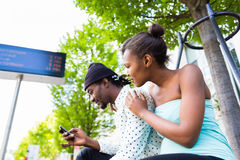 African couple waiting at bus station Royalty Free Stock Photo