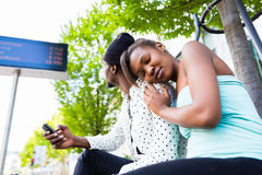 African couple waiting at bus station Stock Photos