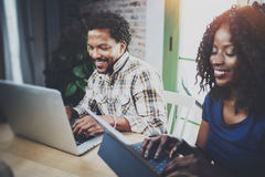 African couple working at a home: black girl using touch tablet and laughing,looking through travel photos together with Royalty Free Stock Photos