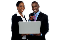 African coworkers operating laptop and pointing Royalty Free Stock Photos