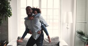 African dad carrying kid daughter giving piggyback ride at home