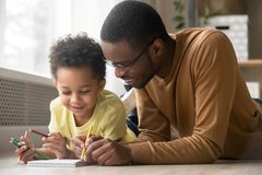 African dad and little toddler son draw with colored pencils. African dad and little creative toddler kid son draw with colored pencils lying on warm floor royalty free stock images