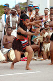 African dance group. A beautiful African woman with traditional clothing dancing in front of a group outdoors on the street Stock Image