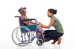 African daughter disabled senior mother. Loving african daughter talking to disabled senior mother on white background Stock Photography