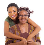 African daughter hugging senior mother. Pretty african daughter hugging her senior mother over white background Royalty Free Stock Image