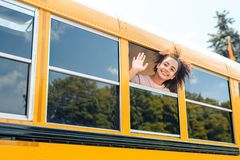 African descent girl going to school by bus with american flag looking out of the window waving smiling joyful
