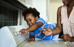 African descent kid helping mom doing the laundry stock photography