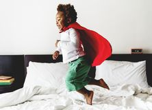 African descent kid jumping on the bed with robe Royalty Free Stock Photo