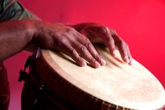 African Djembe Being Played. A African djembe being played isolated on a red background in the horizontal format Royalty Free Stock Image