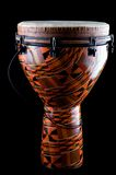 African Djembe Conga. A complete orange African or Latin Djembe conga drum isolated on black background in the vertical format with copy space Royalty Free Stock Image