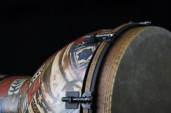 African Djembe Drum Black Bk. African djembe conga drum isolated closeup on its side against a black background in the horizontal format with copy space Royalty Free Stock Images
