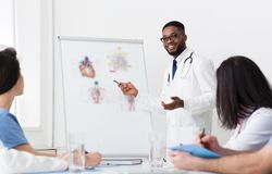 African Doctor Giving Lecture For Colleagues Using Whiteboard stock photos