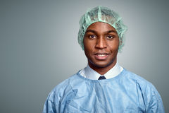 African doctor or male nurse in scrubs. Handsome young African doctor or male nurse in scrubs and a sterility cap looking directly at the camera over a grey Stock Photos