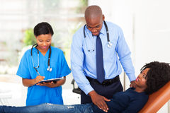 African doctor examining. African doctor and nurse examining female patient in office Stock Images