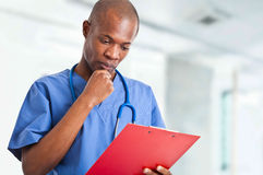 African doctor reading clipboard Royalty Free Stock Photo