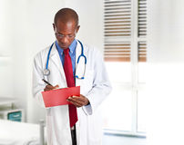 African doctor reading clipboard Stock Photo