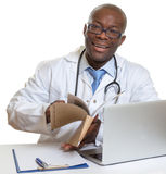 African doctor reading medical records Stock Photo