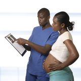 African doctor showing ultrasound image to pregnant woman Royalty Free Stock Images