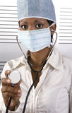 African doctor stethoscope. Young attractive african doctor with face mask holding stethoscope to the patient Stock Images