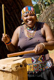 African drum player. Close up portrait of an african zulu tribe woman drum player wearing traditional clothes and playing a drum Stock Photography