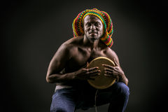 African drummer. Rastafarian african american man playing his drum. Over dark background Royalty Free Stock Photo