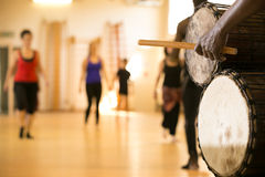 African drums, dance class. Close up of African drums and musician, background with dancing figures Stock Photography