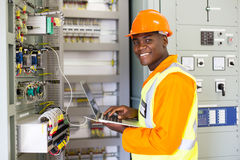 African electrical worker. Using laptop computer checking transformer royalty free stock photography