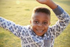 African elementary school boy waving to camera outdoors Royalty Free Stock Image