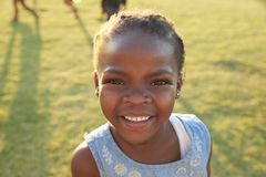 African elementary school girl smiling to camera outdoors Royalty Free Stock Photo