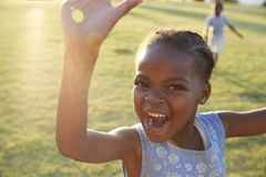 African elementary school girl waving to camera outdoors Royalty Free Stock Image