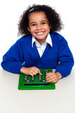 African elementary school kid using a calculator. African elementary school kid using big green calculator. Education and technology Royalty Free Stock Photography