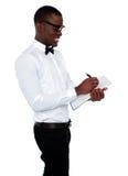 African employee writing on clipboard Stock Photo