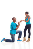 African engagement girlfriend. African men putting engagement ring on his excited girlfriend after she said yes isolated on white Stock Photo