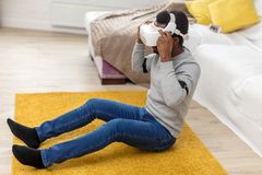 African man wears virtual reality goggles, holds game controllers at home. African entrepreneur in casual clothing wearing goggles with head-mounted display for stock photos