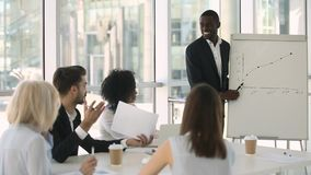 African business trainer asks questions checks knowledge of training participants. African ethnicity male mentor business coach teach employees during business stock video