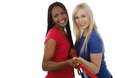 African and european woman hold one rope. African and european women hold one rope isolated on white Stock Photo