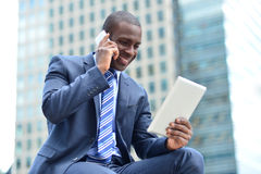 African executive with tablet pc and cellphone. Businessman looking tablet while talking on cell phone Royalty Free Stock Photos