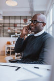 African executive using cell phone while at office Royalty Free Stock Photography