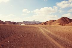 African expedition. Safari and extreme travel in Africa. Drought mountain landscape with dust off road in offroad car expedition stock photography
