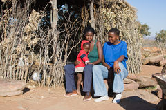 African family. Child, mother and auntie, family portrait, traditional house, Kalahari desert stock photo