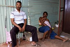 African family. Sitting outside their shack. Alcohol abuse and violence are very common in these poverty stricken townships stock photos