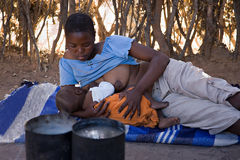 African family. African mother feeding the baby , location Mankodi village , Botswana Stock Image